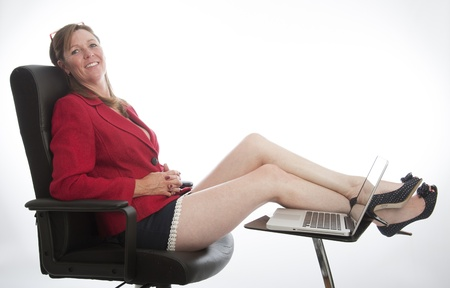 Woman with computer relaxing in a chair with feet up
