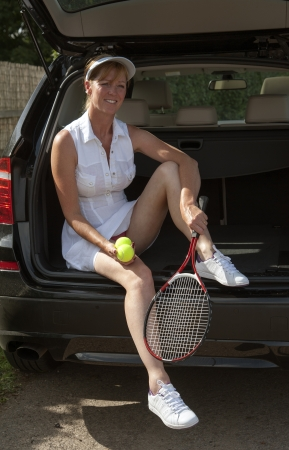 Female tennis player sitting in trunk of car photo