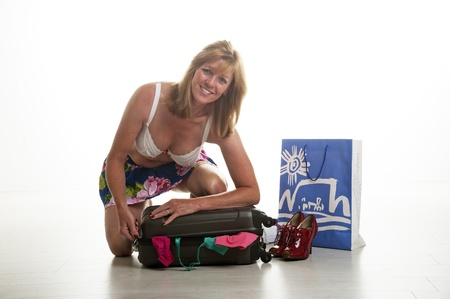 holidaymaker: Holidaymaker trying to close her suitcase