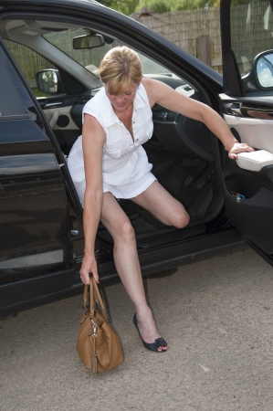 Woman with brown handbag getting out of a car photo