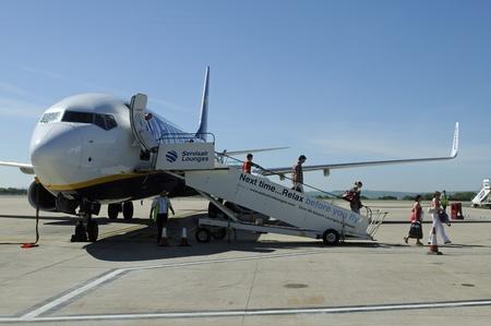 disembark:  passengers disembark from a passenger jet aircraft Editorial