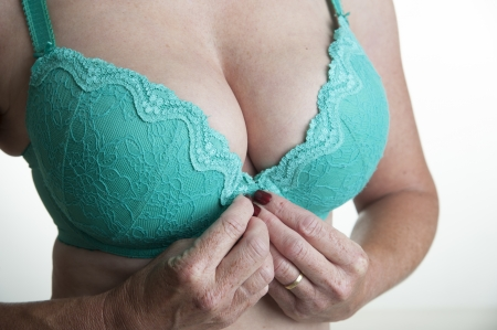 fastens: Woman fastening a green bra