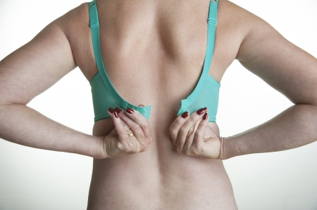 Woman fastening a green bra