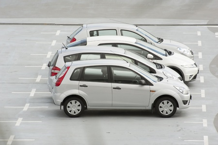 Parked cars in designated spaces of a car park Stock Photo