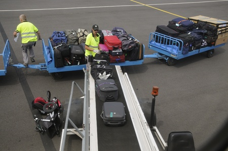 Airport baggage handler loading bags from a trolley
