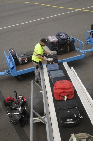 Airport baggage handler loading bags onto aircraft
