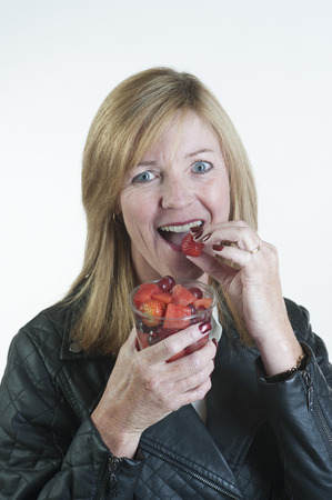 Woman eating fruit salad from plastic cup photo