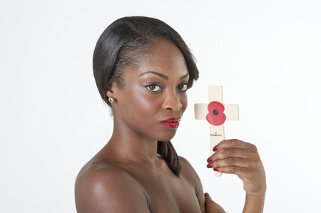 Black woman holds a Remembrance cross and poppy photo