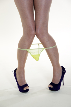 string together: Woman s legs with a pair of yellow panties