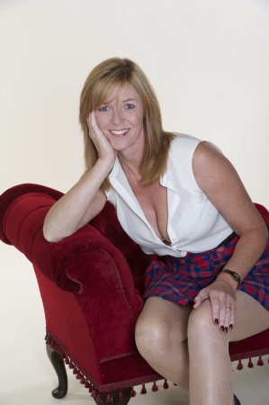 fuller figure: Woman wearing short tartan skirt and white top Stock Photo