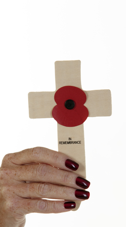Womans hand holding a Remembrance Day cross photo