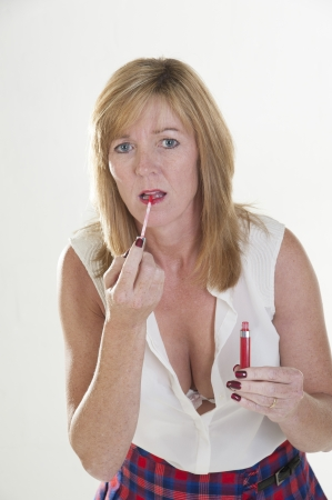 fuller figure: Woman applying lip gloss to her lips