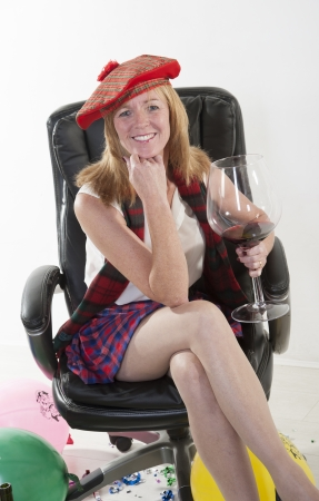 Party goer wearing a kilt and drinking wine