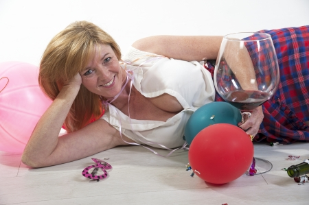 Drinking wine: Female party goer drinking wine laying on floor