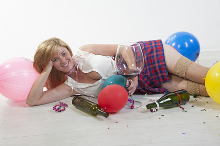 Female party goer drinking wine laying on floor photo