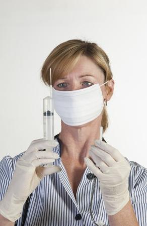 hypodermic syringe: Nurse in surgical gloves holding syringe Stock Photo