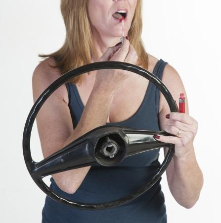 motorist: Female motorist applying make up at the wheel