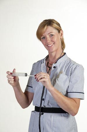 uncovering: Nurse holding a syringe uncovering needle