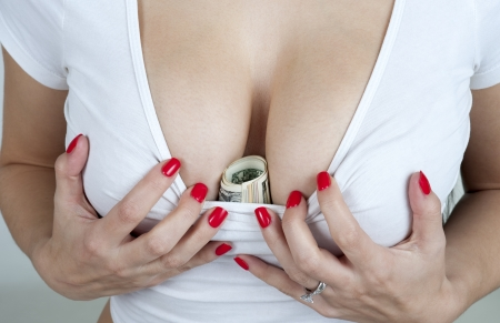 Woman tucking money into her bra for safe keeping