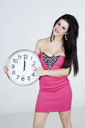 approaching: Woman holding a clock at midnight