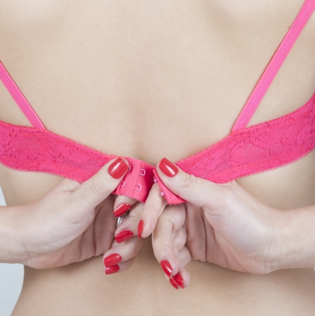 Woman fastening her bra   Female getting dressed