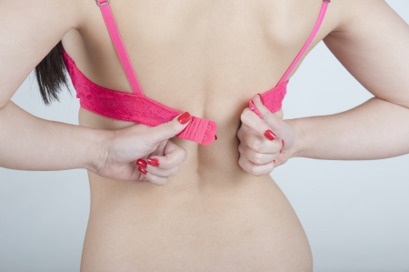 Woman fastening her bra    Female getting dressed Stock Photo
