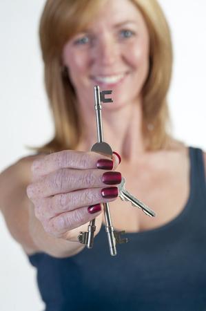 doorkey: Woman holding a key Stock Photo