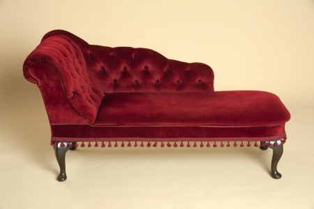 Chaise longue seat covered in a dark red velvet Stock Photo