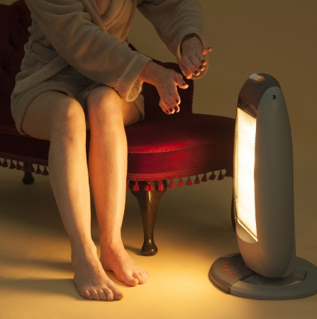 staying: Woman keeping warm by an electric fire