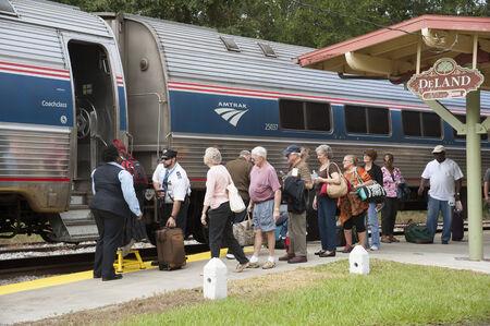 alight: Railroad train passengers board and alight Editorial