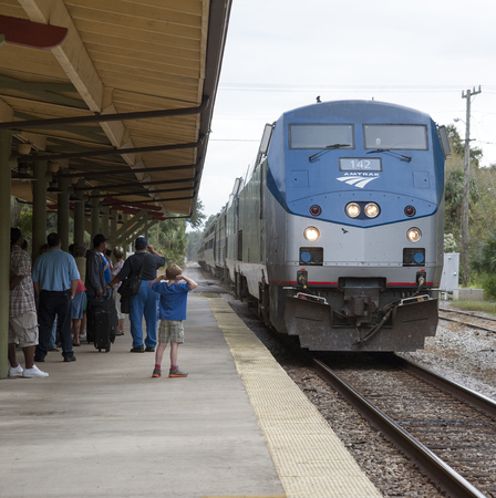 Amtrak train approaching station Boy with hands over ears Editorial