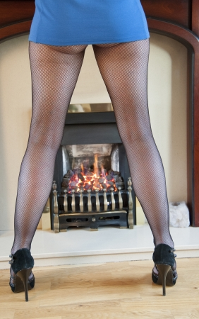 Woman in short skirt warming the front of her legs by a fire photo