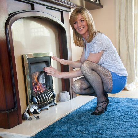 Woman warming her hands by the fire Stock Photo