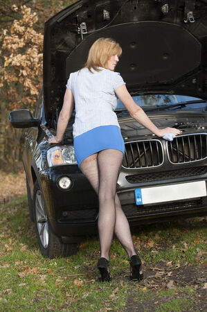 legs open: Female driver with brokendown car Stock Photo