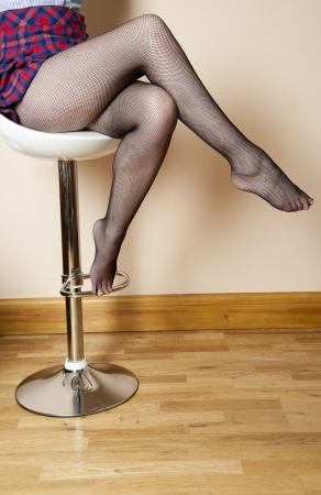 stool: Woman sitting on stool wearing fishnet tights