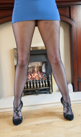 Woman by the fire wearing mini skirt Stock Photo