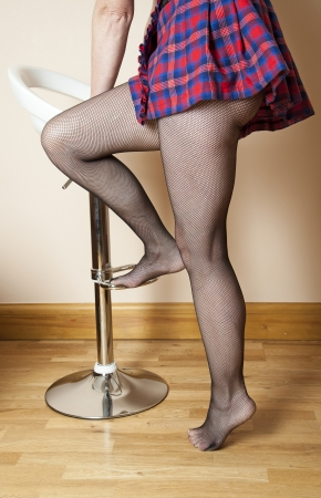 fishnet tights: Woman wearing fishnet tights getting onto a bar stool