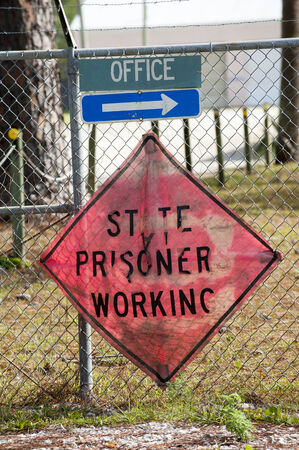 prison fence: State prisoners working sign on prison fence Stock Photo