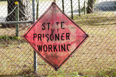 establishment states: State prisoners working sign on prison fence Stock Photo