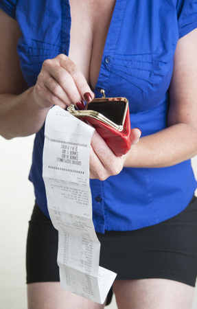 till: Till receipt and red purse in womans hand
