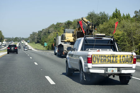 Escort vehicle truck with oversize load on highway America USA