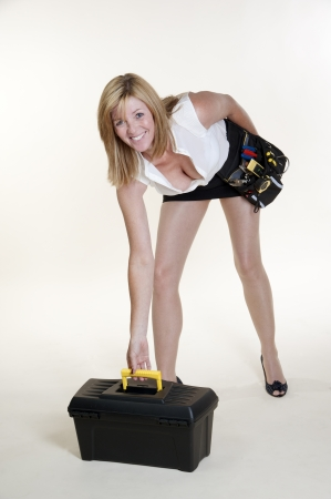 Woman wearing short skirt and long legs with toolbox photo