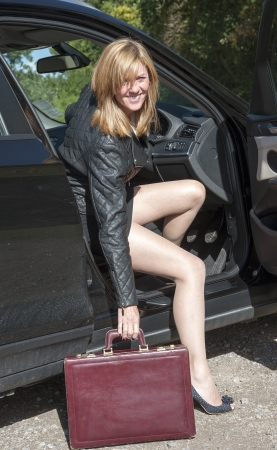 Female motorist with long legs getting out of car Stock Photo