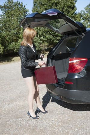Female motorist in short skirt and long legs loading car photo