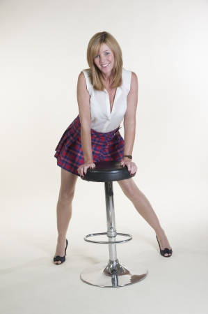 Woman wearing white sleeveless shirt and tartan skirt photo