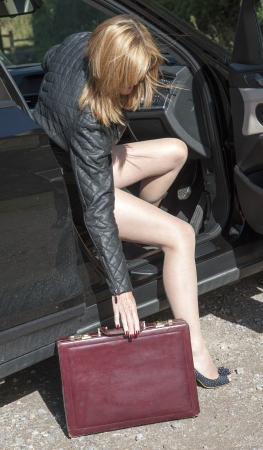 legs open: Female motorist with long legs getting out of car Stock Photo