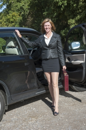 motorist: Female motorist with long legs getting out of car Stock Photo