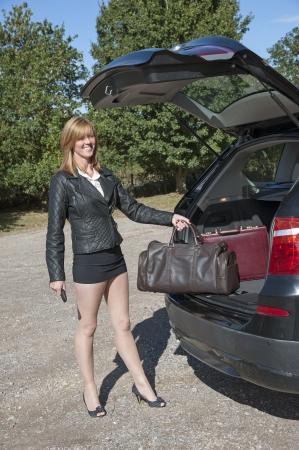 mini jupe: Femme chargement sac de nuit en voiture