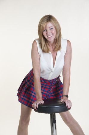 Woman wearing white sleeveless shirt and tartan skirt Stock Photo - 25069923