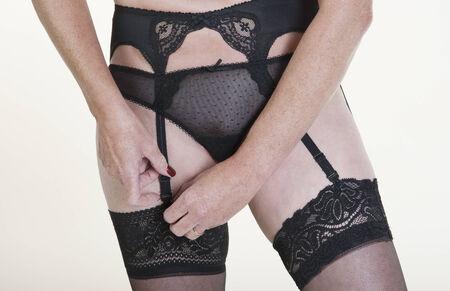 Woman getting dressed fastening suspender
